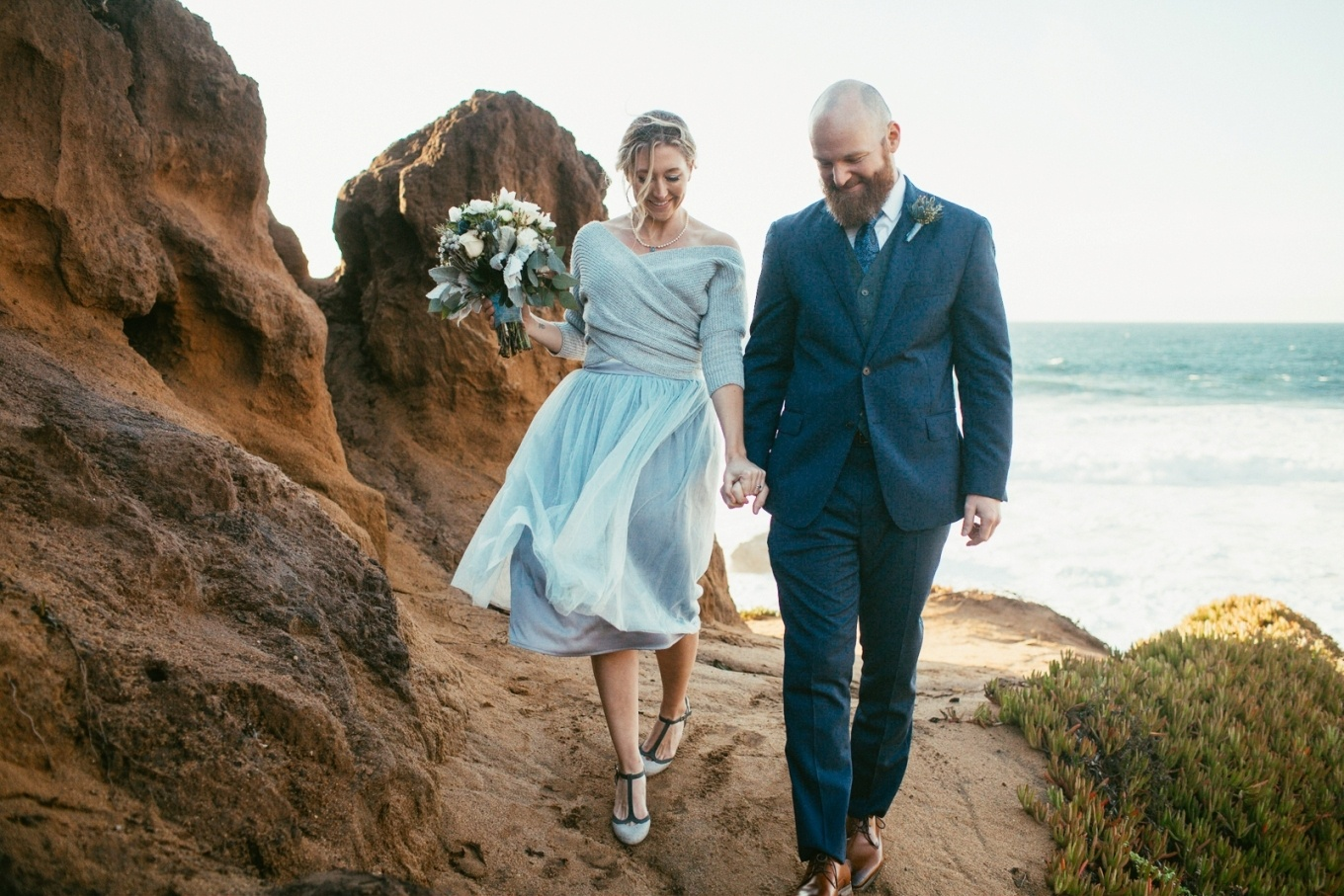 walking on the beach after their elopement ceremony