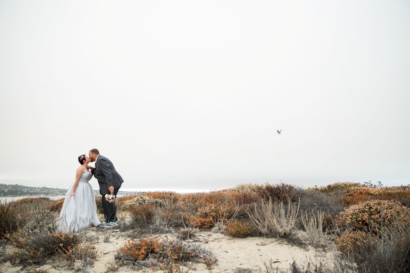 sharing a kiss after eloping on the beach in Monterey