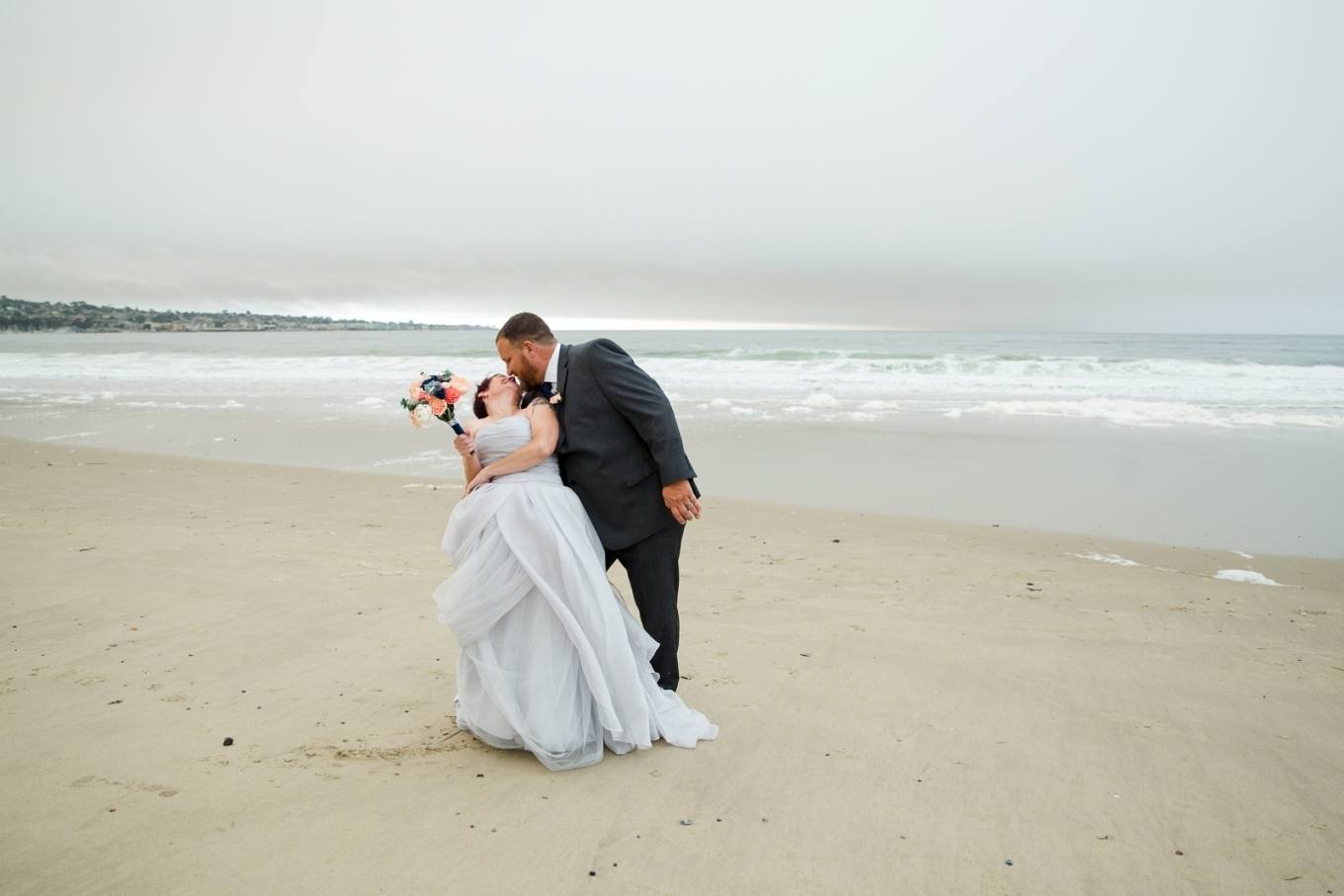 kissing on the beach after their Monterey elopement