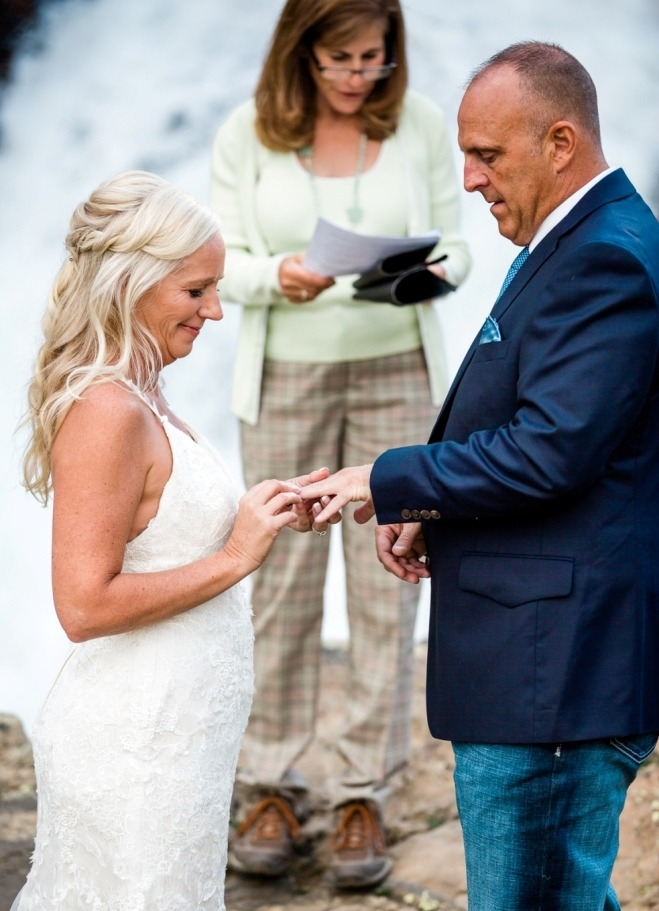 exchanging rings at their Colorado elopement at a waterfall