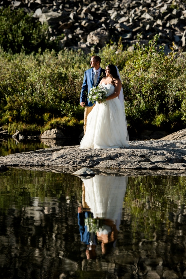 bride and groom on the shores of the mountain lake